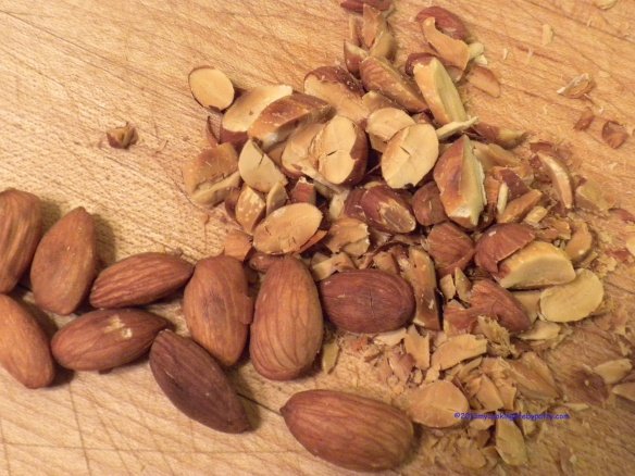 Wash raw almonds in cold water and lay them out in a single layer in a baking pan. Roast at 350 until they smell aromatic and begin to brown. When they are cool, slice them up.