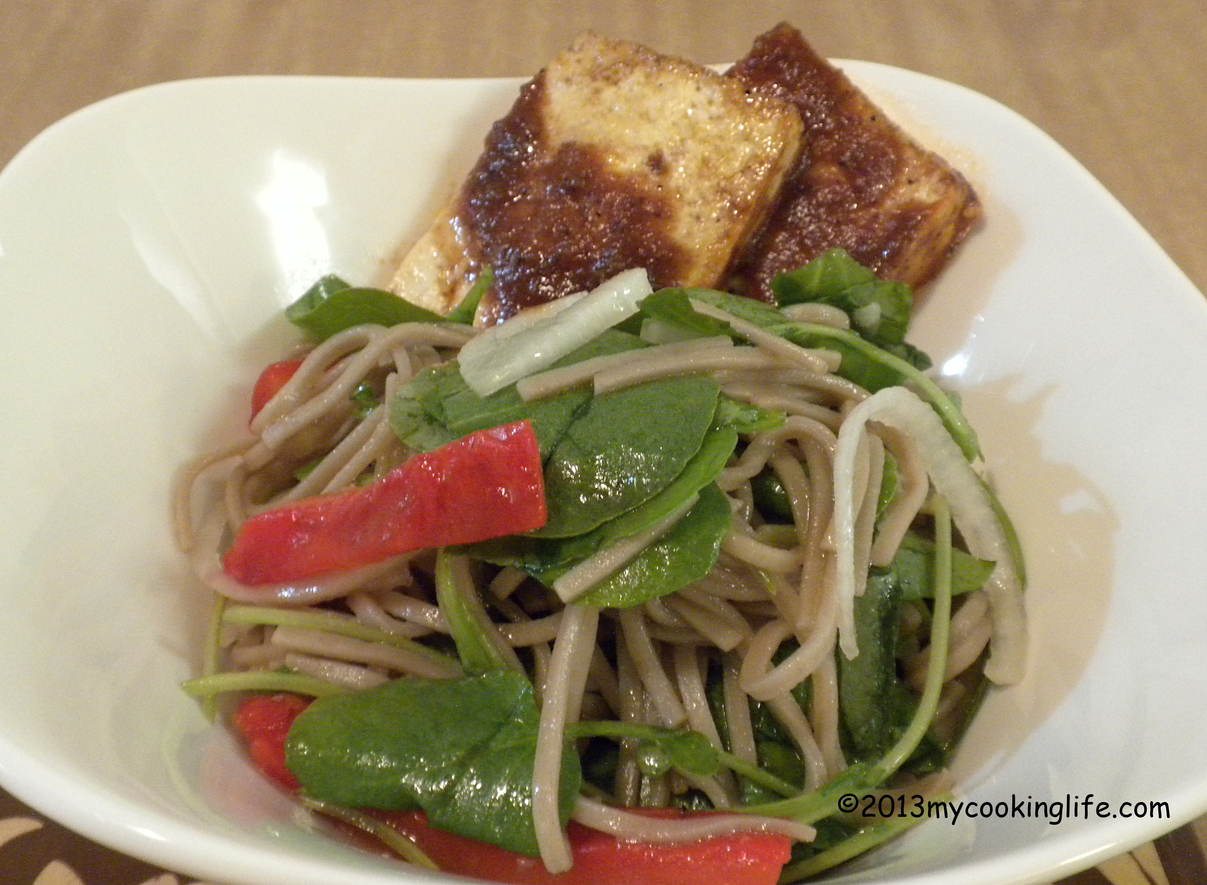 Cold soba salad served with a couple slices of barbecued tofu.
